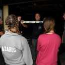 A student group learning how to use a spirit level before installing gutters for a clean water catchment project in Africa