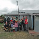 Isaac, Gladys and their large family pose for a photo with teachers and staff from Greenwich Country Day School, USA after they installed a solar power system to their home