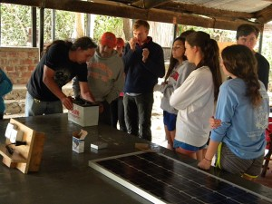 Thiemo explaining to a school group how solar batteries work as part of the solar workshop theory