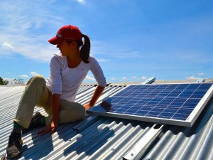 Students installing solar panels to the roof of a poor rural family home as part of Napenda Solar Community in Kenya