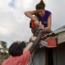 Volunteers in Africa attaching the solar panel brackets to the roof to light up this poor rural family home in East Africa with clean solar power